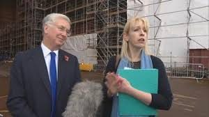 A Government spokesperson conducts an interview on big ships while Defence Secretary looks on.